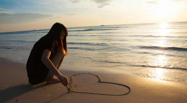 woman drawing a heart in the sand on a tropical beach